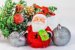 Toy Santa Claus och bollar på av julgranen Royaltyfri Fotografi