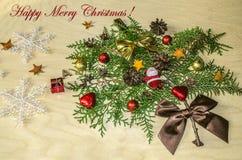 Toy Santa Claus, Schokoladenbälle und -herzen, Kegel und glückliche frohe Weihnachten auf der Niederlassung eines Zypressenbaums Stockfotos