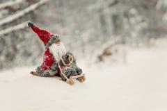 Toy Santa Claus su una slitta in una foresta nevosa Fotografie Stock