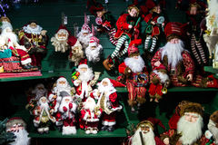Toy Santa Clauses Waiting a Customer. Stall with different kind toy Santa Clauses. Green shelves contrasting with red Santa`s robes. Various of toy kinds related Royalty Free Stock Photo