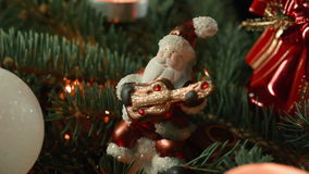 Toy Santa closeup on the Christmas tree with Christmas balls and candle