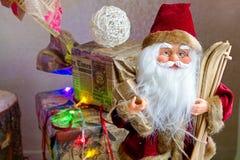 Toy Santa que se sienta debajo del árbol de navidad con los regalos Imagen de archivo
