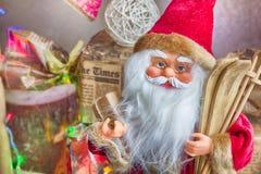 Toy Santa que se sienta debajo del árbol de navidad con los regalos Fotos de archivo libres de regalías