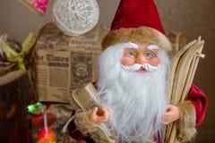 Toy Santa que se sienta debajo del árbol de navidad con los regalos Imagenes de archivo