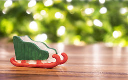 Toy santa sleigh on wooden floor and blur green and light bokeh. Stock Photo