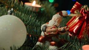 Toy Santa sull'albero di Natale con le palle e la candela di Natale stock footage