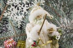 Toy Santa unter Tannenbäumen, Geschenken und Schneeflocken Lizenzfreie Stockbilder