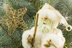 Toy Santa unter Tannenbäumen, Geschenken und Schneeflocken Stockfotos