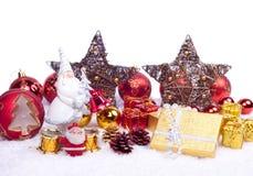 Toy santa with xmas ornaments. Xmas ornaments - santa figure, balls, gifts, stars, candle Stock Photos