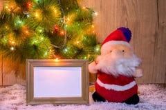 Toy Santa zit onder de boom met houten lay-outs voor een foto of een tekst stock afbeelding