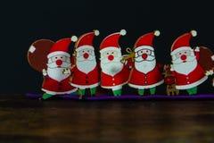 Toy Santas sul fondo della carta e di legno fotografie stock libere da diritti