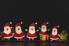Toy Santas sul fondo della carta e di legno fotografia stock libera da diritti