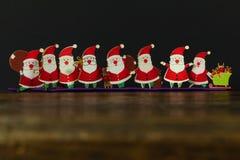 Toy Santas sul fondo della carta e di legno fotografia stock