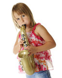 Toy Sax Tooter. A pretty young elementary girl with puffed out cheeks, as she plays a toy saxaphone.  On a white background Stock Photos
