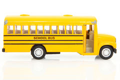 Toy School Buss. Old yellow toy school bus.  Worn with use.  Over white background with reflection Royalty Free Stock Images