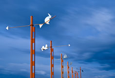 Toy Shaped Vanes. Some toy shaped vanes located on red poles with a blue sky in motion as a background. Long time of exposure used to increase the sense of Stock Images