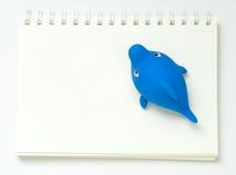 Toy Shark de flottement de plastique sur un carnet Images stock