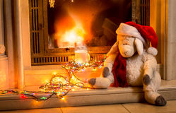 Toy sheep sitting next fireplace at new year Royalty Free Stock Photo