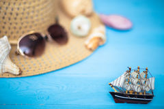 Toy ship, blurred hat, sunglasses and shells on back Stock Photo