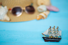 Toy ship, blurred hat, sunglasses and shells on back Stock Photography