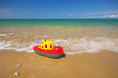 Toy ship on the sea shore. Royalty Free Stock Image