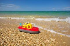 Toy ship on the sea shore Stock Photos