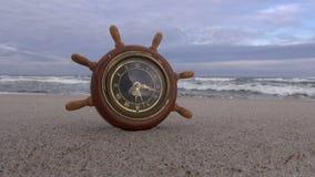 Toy ship wheel clock on the beach stock footage