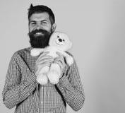 Toy Shop Mann hält Teddybären betreffen blauen Hintergrund Mann mit Bart Lizenzfreie Stockfotografie