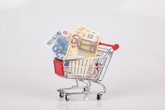 Toy shopping cart filled with euro notes on white background Royalty Free Stock Images