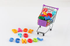 Toy shopping cart filled with letters and numbers - back to scho Royalty Free Stock Photography