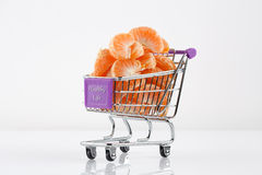 Toy shopping cart filled with mandarin slices Royalty Free Stock Photo