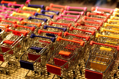 Toy shopping carts on display. In shop window. Multiple colours on white/gray steel mesh shelf Royalty Free Stock Photo