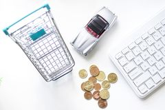 Toy shopping trolley, toy car and coins. Toy shopping trolley, toy car, computer keyboard and coins on a white surface stock photos