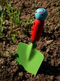 Toy shovel with green blade and ladybug handle jabbed in garden soil. End of a wooden handle is blue smiley royalty free stock photography