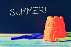 Toy shovel and pail, and word summer written in a chalkboard. A blue toy shovel and an orange toy pail on a blue school desk, and the word summer written in a royalty free stock image