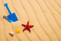 Toy, shovel with sea star on a sunny beach Royalty Free Stock Images