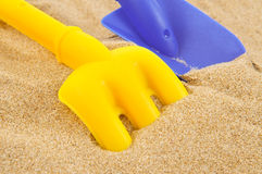 Toy shovel and toy rake on the sand Royalty Free Stock Photo
