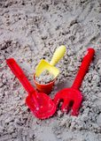 Toy Shovels, Bucket, and Rake in Sand. Toy Shovels (yellow and red), Bucket, and Red Rake in Sand stock photography