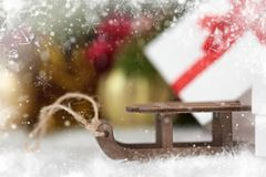 Toy sleigh and Christmas decorations as background, decorated with snow Stock Photo