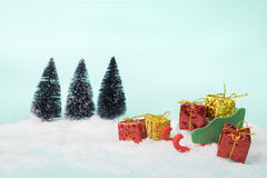 Toy sleigh and gift boxes on sweet veintage green bright turquoi Stock Image