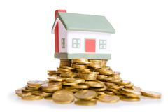 Toy small house standing on a heap of coins. Royalty Free Stock Photos