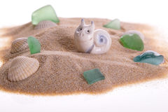 Toy snail on sand near cockles and stones Royalty Free Stock Photography