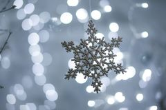Toy snowflake on bokeh background. Toy snowflake on a background of lights stock photo