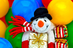 Toy Snowman with Christmas gifts and colorful balloons. Smiling Snowman toy in scarf and black hat with gift box in colorful balloons Royalty Free Stock Photos