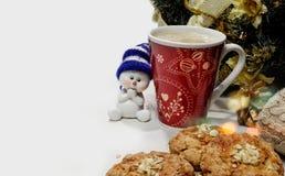 Toy Snowman debajo de un árbol de navidad con café y galletas Foto de archivo