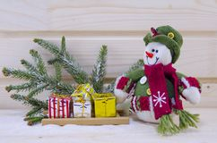 Toy Snowman entre abetos y presentes Foto de archivo