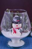 Toy snowman in a glass vase covered with snow Royalty Free Stock Images