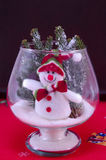 Toy snowman in a glass vase on a red tablecloth Royalty Free Stock Images