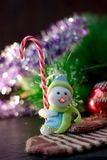 Toy snowman holding christmas candy cane in hands. Toy snowman holding christmas candy cane in hands Stock Images