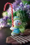 Toy snowman holding christmas candy cane in hands. Toy snowman holding christmas candy cane in hands Royalty Free Stock Photos